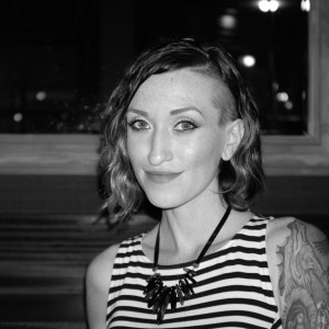 A black and white photograph of Genevieve. She is smiling at the camera and has a shorter wavy haircut with one side of her head shaved. She is wearing a black and white striped top and a necklace with black crystals that hang down. Her left arm is tattooed.