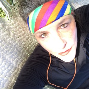 Image of Sara Seinberg. She is white, wearing a rainbow headband, looking up at the camera, wearing a black jacket and orange headphones.