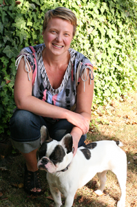 Dana Sturtevant - she is white with blond, short hair. In this picture she is kneeling in front of a wall of green leaves. She is wearing a sleeveless shirt and jeans, and is smiling at the camera. She's petting a very cute black and white French bulldog.