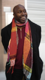Image is of the author - Michael Hayes is a black man with a bald head, and he is grinning widely. He wears a black jacket, burgundy shirt, and a multicolored scarf.
