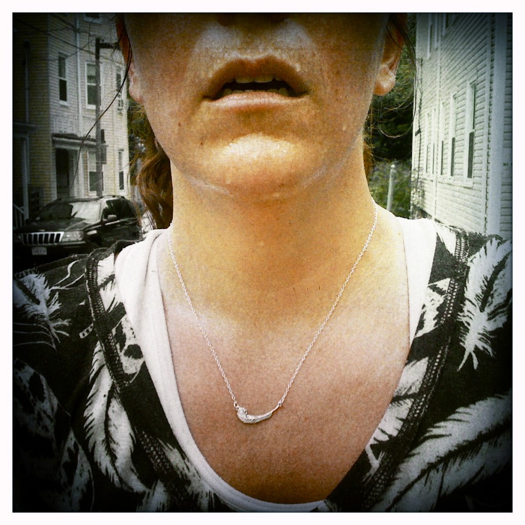 An image of the author's face from the nose down to her chest. She is wearing a small necklace and a black and white patterned shirt.