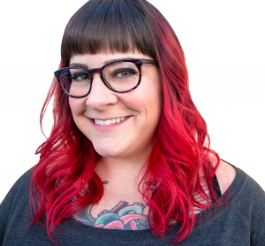 Amber Karnes [in this picture, Amber, a white, cisgender, fat woman grins into the camera. She has wavy hair with bangs that fades from dark brown to a bright red. She's wearing a gray sweater and has a colorful chest tattoo peeking out of her shirt.]