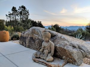 Image: Photograph of a sculpture in front of a rock and a beautiful California central coast/desert background with mountains and a sunset in the distance