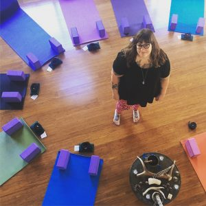 Image: photograph of Amber standing in a circle of colorful yoga mats, she is looking up at the camera