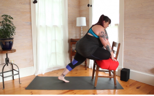 Image description: Amber, a fat, white, female bodied yoga practitioner demonstrating pigeon pose with a chair and a bolster.