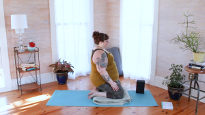 Image description: Amber, a fat, white, female bodied yoga practitioner in hero pose supported with blocks