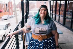 Image description: photo of Amber looking upward and grinning. She is a white, fat woman with green hair, glasses, and tattoos. She's wearing a grey tshirt with a cartoon of Pusheen the cat reading a book, a brown belt, and a navy blue skirt with white polka dots. Photo by Jaime Patterson, Hidden Exposure Photography