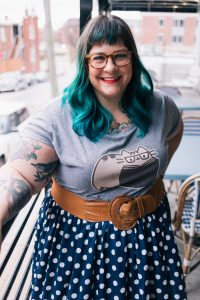 A photograph of Amber Karnes. She is a fat, white woman with green hair, dark bangs, glasses, and tattoos. She is smiling at the camera and leaning on a railing. She's wearing a grey shirt with pusheen the cat on it, a brown belt, and a navy blue skirt with white polka dots.