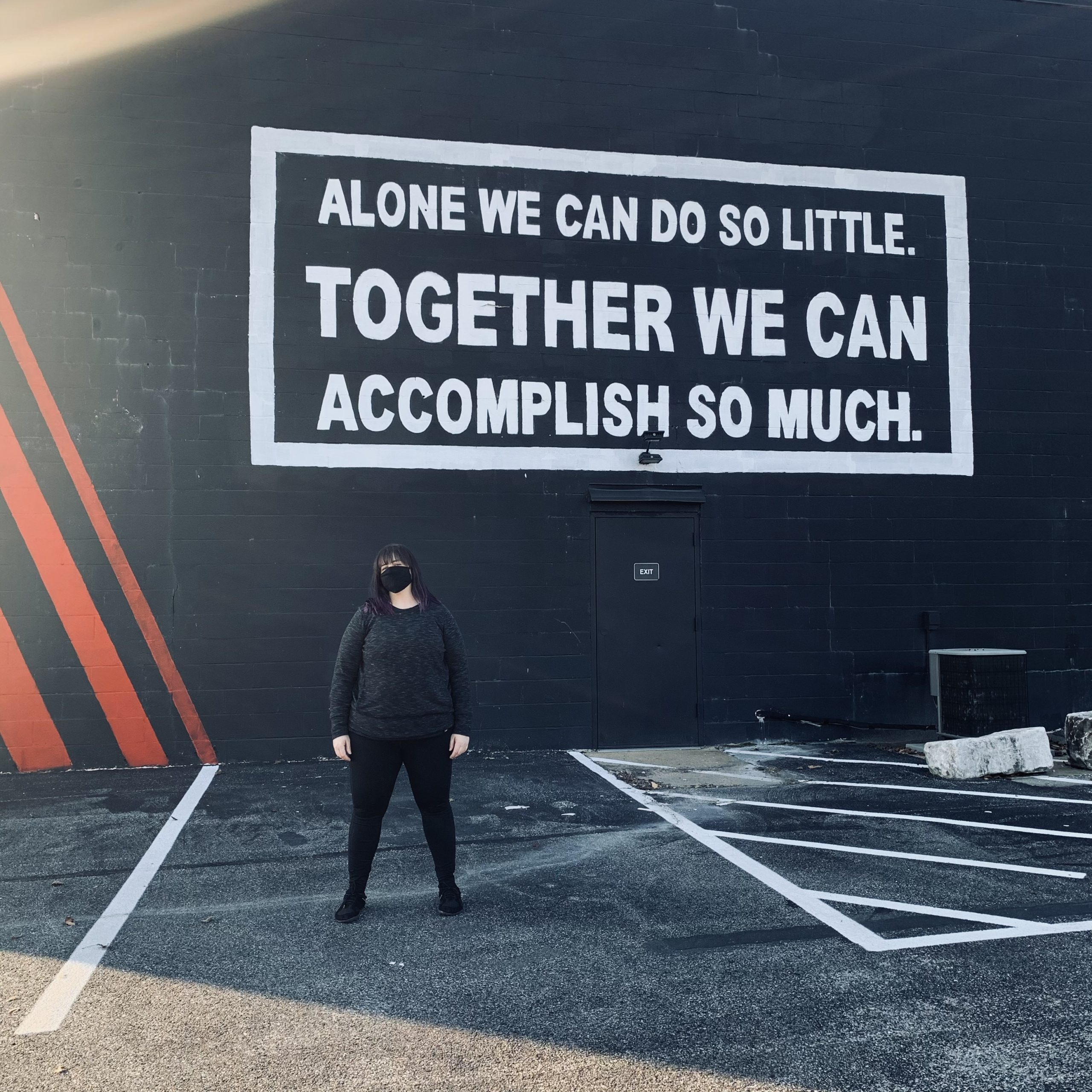 "Amber Karnes stands in an empty parking space in front of a mural. The mural is white text on a black background that says ""Alone we can do so little. Together we can accomplish so much."""